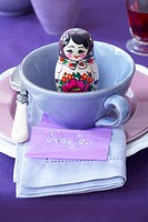 A place setting with a Russian doll in the cup