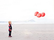 Portrait of boy on beach with red balloons
