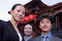 Portrait of three businesspeople with Chinese architecture in background.