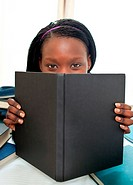 Cute afro-american teenager behind a book looking at the camera against white background