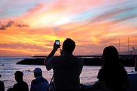 Tourist taking picture of a spectacular sunset at Waikiki beach in Honolulu, Hawaii.