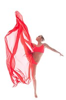 Attractive gymnast dancing with cloth in studio