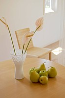 Pears and flowers in vase on table
