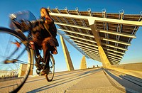 "Cyclist passing by the solar panels at the Forum Esplanade, designed by architects Elias Torres and Jose Antonio Martinez Lapena for the """"Forum Barce..."