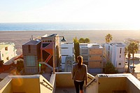 One woman leaves Palisades Park on sunny afternoon, with modern architecture beachfront homes and Pacific Ocean in distance, Santa Monica, City of Los...