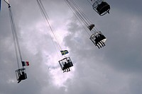 Riders on the Starflyer, near the London Eye, in the heart of the city, eighty metres high, at dusk.