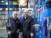 Mature engineers working in engineering factory, portrait