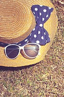 Pretty vintage straw hat with polkdot bow lying on dry Australian grass background. Travel outback australia.