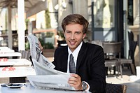 Young man cheerful reading newspaper
