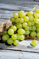 Seedless white grapes on jute and wooden table
