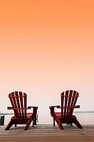 Two chairs on a deck overlooking the ocean, Halifax, Canada, under a saffron sky