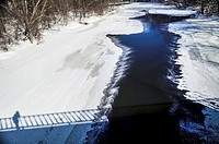 A photographer, me, catches his shadow on the bridge over a nearly frozen Thames on the coldest day of a long winter, -- 30C, Ontario, Canada. Snow an...