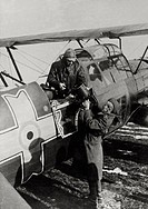 Airman giving a movie camera to a pilot. Airman giving a movie camera to a pilot of a Romanian reconnaissance plane heading behind the Russian lines o...