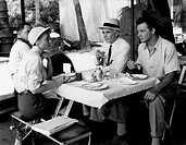 Donna Reed, Leo Genn and Cornel Wilde in Beyond Mombasa. American actress Donna Reed (Donnabelle Mullenger) having lunch with British actor Leo Genn a...