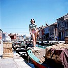British singer Sandie Shaw, nom de plume of Sandra Ann Goodrich, wearing a tied shirt and a pink bikini onboard an old boat, anchored in a drain; ofte...