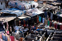 Indian hand laundry, Dhobi Ghat, and laundrymen using traditional flogging stones to wash clothing at Mahalaxmi, Mumbai, India