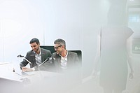 Male business colleagues using digital tablet in office