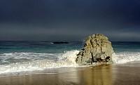 A wave impacting a rock on Garrapata State Beach. Monterey coast, California, United States.
