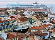 Cityscape of central Lisbon with giant cruise ship Oceana docking on the waterfront. Seen from viewing platform at top of Elevador de santa Justa, Por...