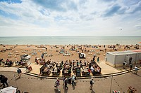 People eating on the beach promenade, Brighton, UK