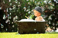 Boy in fedora in bubble bath