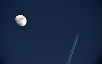 12.03.2014, Germany, a plane flies over Unkel at high altitude and produces contrails in the sky, seemingly close to the moon - Unkel, Rhineland-Pala,...