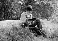 Seventies, black and white photo, people, young woman sits on a meadow reading a magazine, cigarette, rest, blouse, trousersuit, aged 25 to 30 years, ...