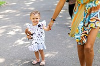 Mother and daughter walking on sidewalk