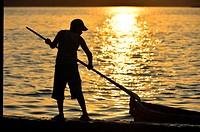 Sunset silhouette of boy , El Peten, Flores, Lago de Peten Itza, Guatemala, Central America.
