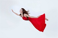 a woman in a red dress floating horizontally in the air