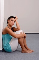 Young pensive woman sitting on floor of an empty room