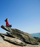 Asian woman meditating on rock formation