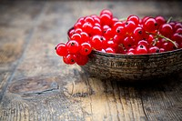 Bowl of red currants, Ribes rubrum, on dark wooden table, partial view