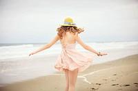 Rear view of teenage girl strolling on beach, Hampton, New Hampshire, USA