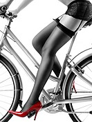 Legs of a woman in black stockings and sexy red high heel shoes riding a bicycle isolated on white background. Black and white with red color.