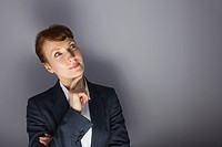 Businesswoman in suit thinking with finger on chin