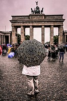Woman standing with a Souvenir Berlin Umbrella near the Brandenburg Gate.