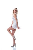 Flirtatious slim girl posing in white short dress