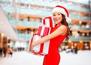 christmas, holidays, celebration and people concept - smiling woman in red dress with gift boxes over shopping center background