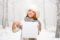 Young girl with blank poster at snowy forest