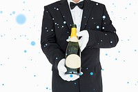 Waiter holding champagne bottle against snow falling
