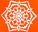 white snowflake on orange paper