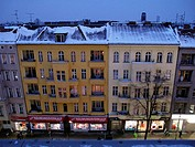 Bird's eye view of facades of buildings in Berlin covered with snow at twilight.