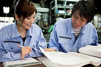 Two Factory Workers Reading Documents