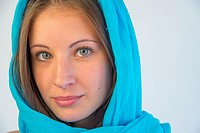 Portrait of blonde young woman wearing turquoise shawl.