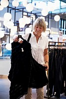Senior woman in clothes shop