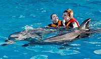 Dolphin therapy for children. Child and carer swimming with dolphins as part of dolphin-assisted therapy for children. Children with conditions such a...