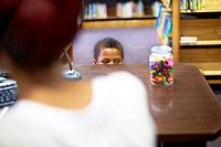 Boy in library peeking at candy jar