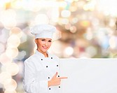 cooking, advertisement and people concept - smiling female chef, cook or baker pointing finger to white blank board over holidays lights background