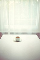 Single coffee cup on table by window